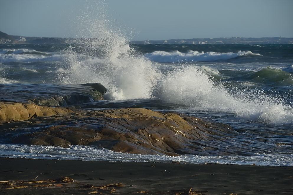 岩場に砕ける波と強風で飛ぶ波飛沫